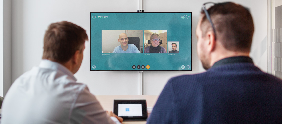 Image of two colleagues having a video conference with three other people